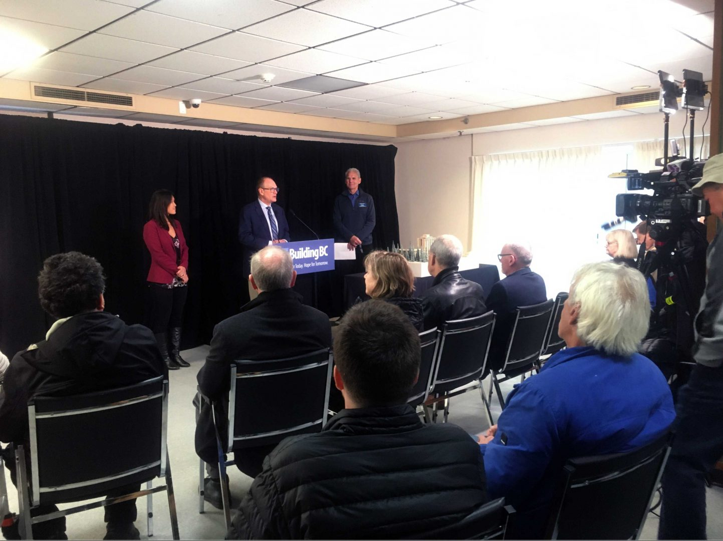 Kiwanis Media Launch three people standing at a podium with cameras facing them